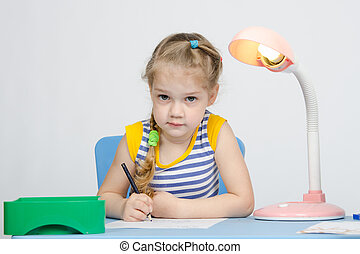 Girl sits at the table and draws a blue pencil