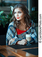 Girl sits at the table wrapped in a blanket.