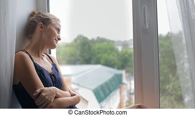 Girl sits by the window and smiles