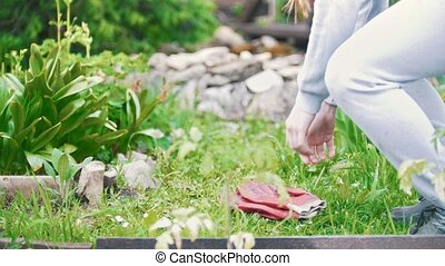 Girl sits down and puts on garden gloves, summer day,...