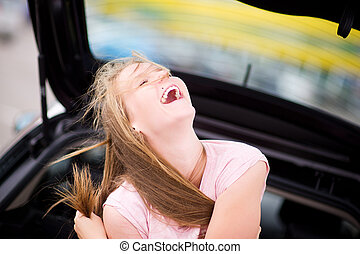 girl sits in a car on a summer day and laughs out loud, squinting her eyes