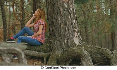 girl sits in a large pine tree forest roots slow motion