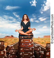 Girl sits in a pose of yoga on suitcases.