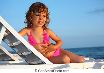 girl sits in chaise lounge on seacoast