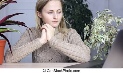 Girl sits in front of a laptop monitor, rubs her hands and is nervous while waiting for an email.