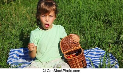 girl sits in grass, eats sweet cherry from basket and smiles
