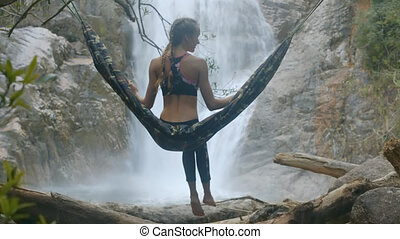 Girl Sits in Hammock Hanging on Tree by Waterfall