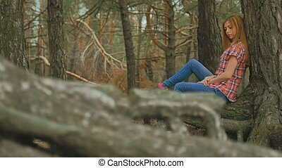 girl sits in large pine tree forest roots slow motion