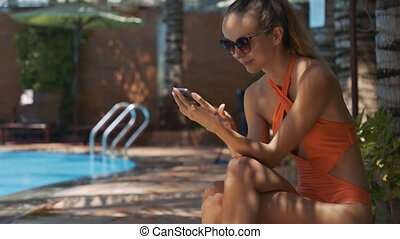Girl Sits in Shady Place at Pool and Texts on Phone - blond...
