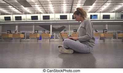 Girl sits in the terminal on the floor of the airport works with a laptop while waiting for the flight.