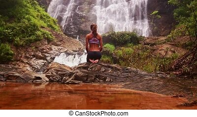 Girl Sits in Yoga Pose behind Red Lake against Waterfall