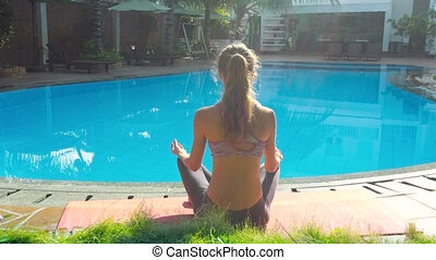 girl sits in yoga pose Lotus by swimming pool backside view