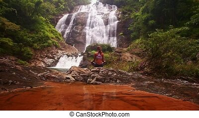 Girl Sits in Yoga Pose near Red Transparent Lake at Waterfall