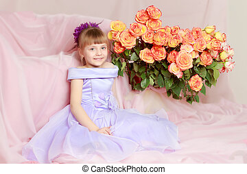 Girl sits next to a bouquet of flowers.