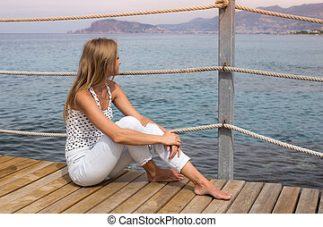 Girl sits on a pier by the Sea and looks at the mountains