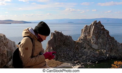Girl sits on a rock by the sea on a background of amazing landscape, uses phone