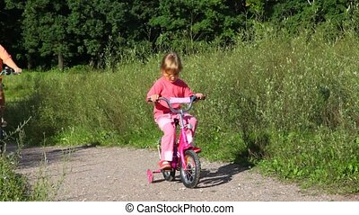 girl sits on bicycle, woman rides pass in park