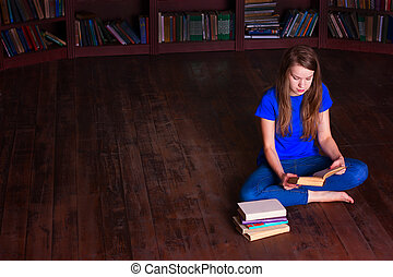 girl sits on floor in the library