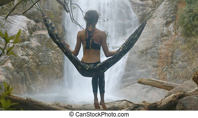 Girl Sits on Hammock Watches Waterfall Backside View