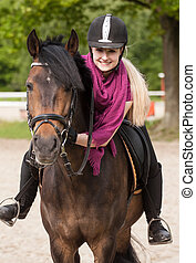 Girl sits on her horse - Girl sits on her brown horse (New-...