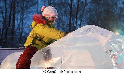 girl sits on ice sculpture, slides off downwards, father...