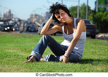 girl sits on lawn at road in city