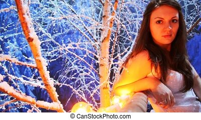 girl sits on lighted balcony in snowy birch forest at night