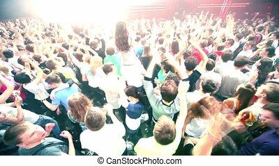 Girl sits on mans shoulders among people at rave party, DJ Armin Van Buuren on stage