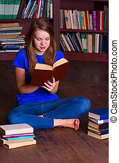 girl sits on the floor in library