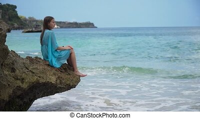 Girl sits on the rock and looks at the sea. Bali, Indonesia