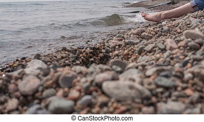 Girl sits on the shore of Baikal
