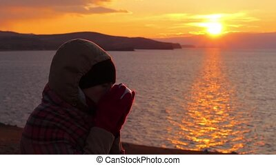 Girl sits on the shore of the sea and drinks a hot tea. Beautiful golden sunset