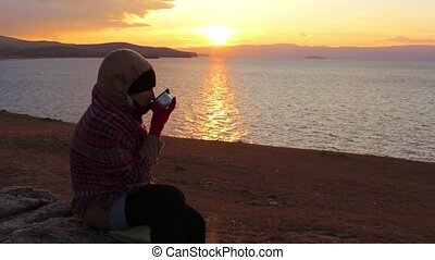Girl sits on the shore of the sea and drinks a hot tea. Amazing golden sunset