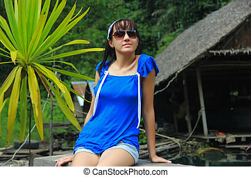 girl sits on the shores of lake