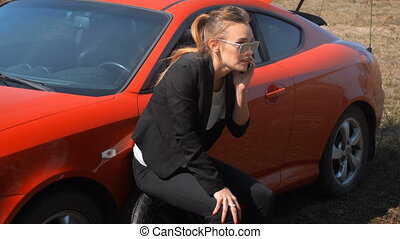 girl sits on the spare wheel of the car and talking on the phone