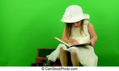 Girl sits on the suitcases and reads the book. Smalll girl...