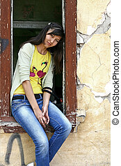 Girl sits on the window sill in a deserted building