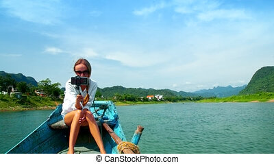 girl sits on wooden boat bow makes selfie against river