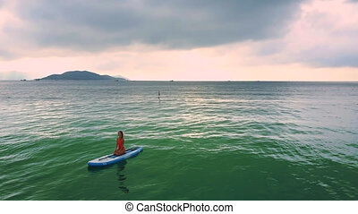 girl sits resting on paddleboard among ocean against pink sky