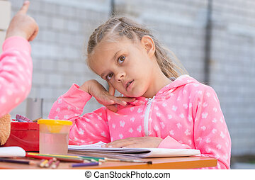 Girl sits thoughtfully at the table with accessories for painting