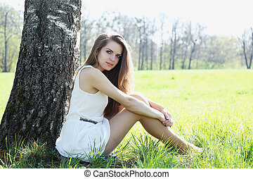 girl sits under the tree in the meadow