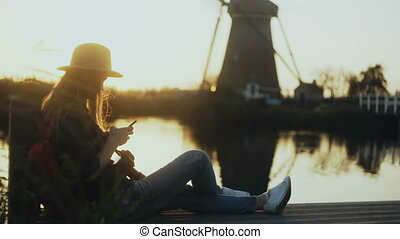 Girl sits with smartphone on sunset lake quay. Woman using...