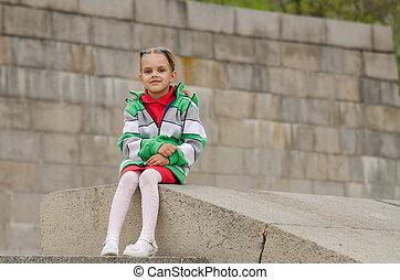 Girl sitting a granite embankment on ramp
