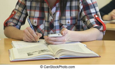 Girl sitting at a desk writes text in a copybook - The girl...