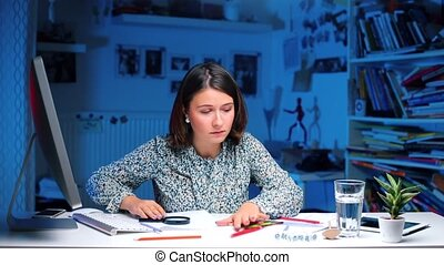 Girl sitting at a table in the office, looking for a mobile phone on the table.