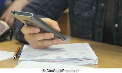 Girl sitting at desk and holding a mobile phone