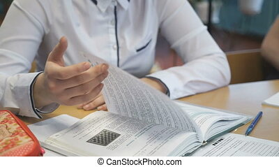 Girl sitting at desk leafing through a textbook