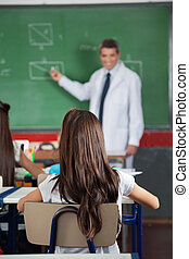 Girl Sitting At Desk With Teacher Teaching In Background