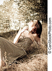 Girl sitting at grass. Photo in old image style.
