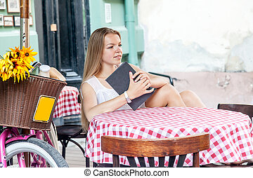 girl sitting at summer terrace and reading book